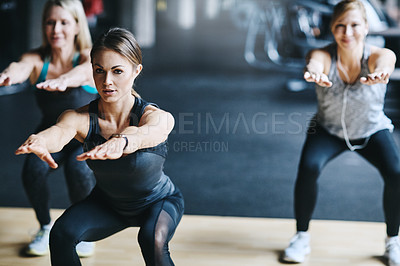 Buy stock photo Cropped shot of three attractive and athletic women working out in the gym