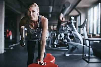 Buy stock photo Cropped shot of an attractive young woman listening to music while working out with a dumbbell in the gym