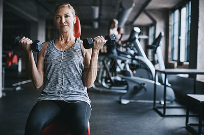 Buy stock photo Cropped shot of an attractive young woman listening to music while working out with dumbbells in the gym