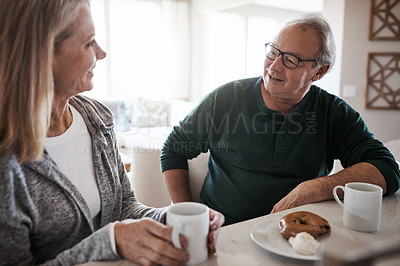 Buy stock photo Shot of a mature couple having coffee and a snack together during a relaxed day at home