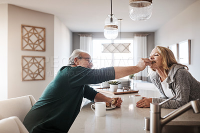 Buy stock photo Shot of a senior man lovingly feeding his wife a taste of his snack during a relaxing day at home