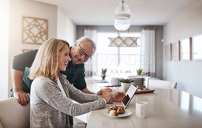 Buy stock photo Shot of a mature woman using a digital tablet during a relaxed morning at home