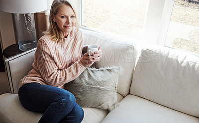 Buy stock photo Shot of a mature woman relaxing on the sofa at home with a cup of coffee