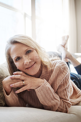 Buy stock photo Shot of an attractive mature woman relaxing on the sofa at home
