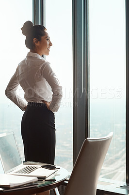Buy stock photo Rearview shot of an attractive young businesswoman standing with her hands on her hips in the office