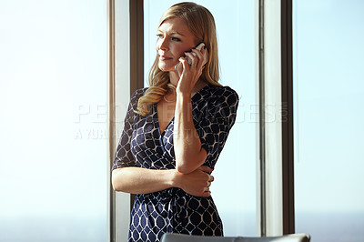 Buy stock photo Cropped shot of an attractive young businesswoman making a call while standing in her office