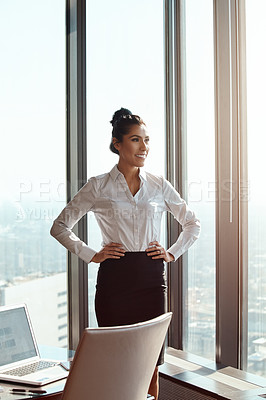 Buy stock photo Cropped shot of an attractive young businesswoman standing with her hands on her hips in the office