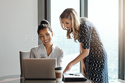 Buy stock photo Cropped shot of two attractive young businesswomen working in a modern office
