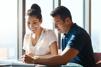 Buy stock photo Shot of a young man and woman going through paperwork together in an office