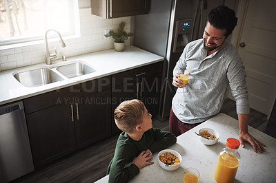 Buy stock photo High angle shot of a young boy and his father having breakfast in the kitchen