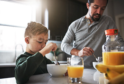 Buy stock photo Cropped shot of a young boy and his father having breakfast in the kitchen
