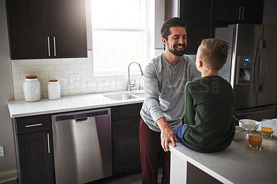 Buy stock photo High angle shot of a handsome young man talking to his son while standing in the kitchen