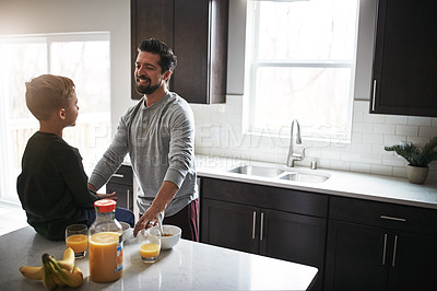 Buy stock photo High angle shot of a handsome young man talking to his son while having breakfast  in the kitchen