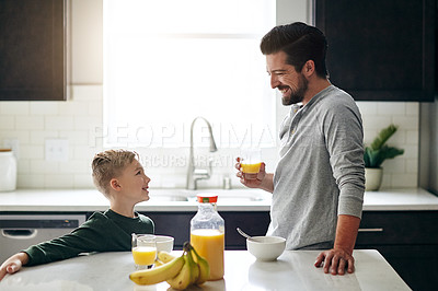 Buy stock photo Cropped shot of a handsome young man talking to his son while having breakfast  in the kitchen