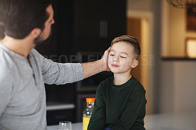 Buy stock photo Cropped shot of a handsome young man talking to his son while standing in the kitchen
