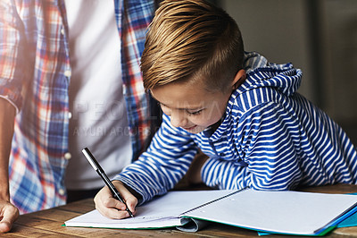 Buy stock photo Shot of a little boy doing his homework with his father at home