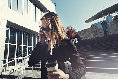 Buy stock photo Shot of a young businesswoman using a mobile phone while walking through the city
