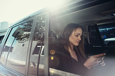 Buy stock photo Shot of a young businesswoman using a mobile phone while traveling in a car