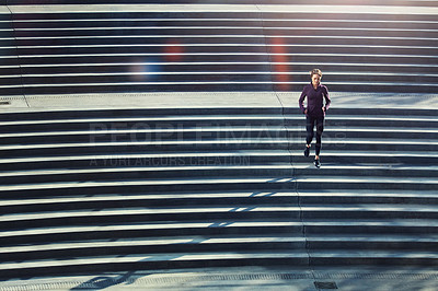 Buy stock photo High angle shot of an attractive young sportswoman running up and down stairs outside