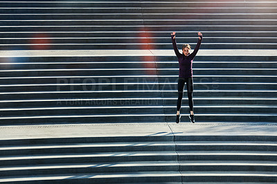 Buy stock photo Full length shot of an attractive young sportswoman doing jumping jacks on outside stairs