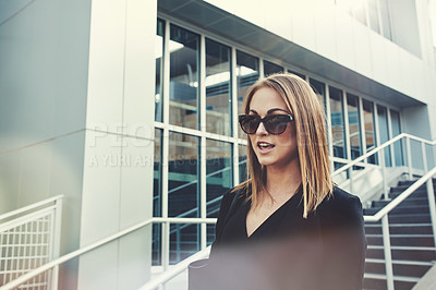 Buy stock photo Shot of a beautiful young businesswoman walking through the city