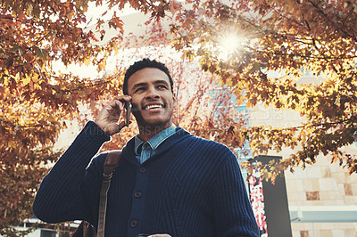 Buy stock photo Shot of a young businessman using a mobile phone while walking outdoors