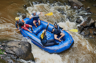 Buy stock photo Shot of a group of young male friends white water rafting