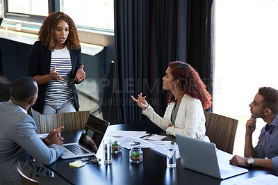 Buy stock photo High angle shot of an attractive young businesswoman addressing her colleagues in the boardroom