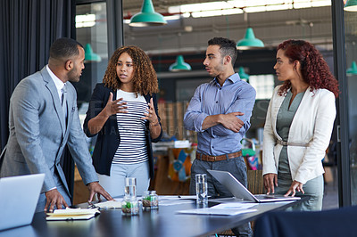 Buy stock photo Cropped shot of a group of young businesspeople talking while standing in the boardroom