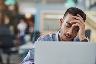 Buy stock photo Shot of a young businessman looking stressed out while working on a laptop in an office