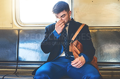 Buy stock photo Shot of a irritated looking young man blowing his nose while being seated inside of a train to get to work