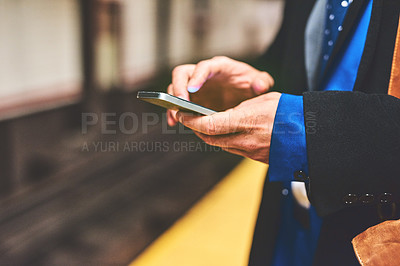 Buy stock photo Shot of an unrecognizable man texting on his phone while waiting for a train to get to work in the morning