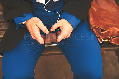 Buy stock photo Shot of an unrecognizable man listening to music while being seated on a bench outside in the morning