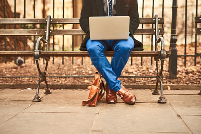 Buy stock photo Shot of an unrecognizable man working on his laptop while being seated on a bench outside during the day