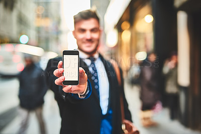 Buy stock photo Portrait of a cheerful young man holding up a cellphone and showing the screen to the camera outside in the city during the day