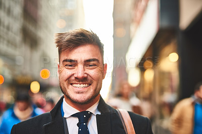Buy stock photo Portrait of a cheerful young businessman standing in the middle of the busy streets of the city during morning hours