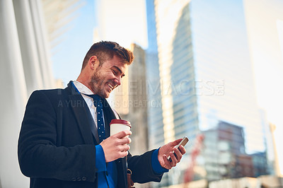 Buy stock photo Shot of a cheerful young man texting on his phone while drinking coffee at work during the morning hours
