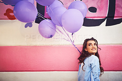 Buy stock photo Cropped shot of a beautiful young woman holding purple balloons against a wall outside