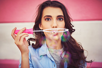Buy stock photo Cropped shot of a beautiful young woman blowing bubbles outside