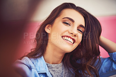 Buy stock photo Cropped shot of a beautiful young woman taking a selfie against a wall outside
