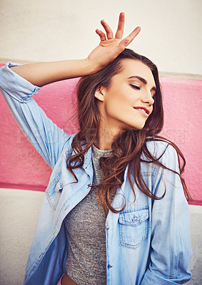 Buy stock photo Cropped shot of a beautiful young woman posing against a wall outside