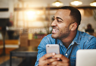 Buy stock photo Shot of a handsome young man using a cellphone in a cafe