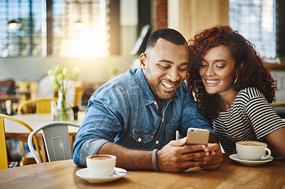 Buy stock photo Cropped shot of an affectionate young couple looking at a cellphone while sitting in a coffee shop