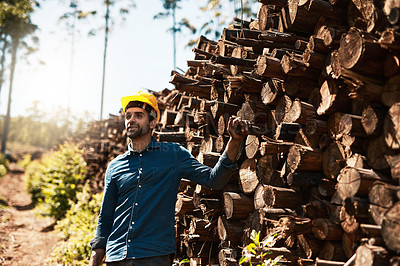Buy stock photo Cropped shot of a lumberjack standing in front of a pile of wood