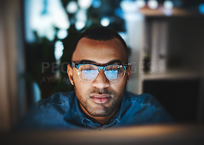 Buy stock photo Shot of a young businessman using a computer during a late night at work in a modern office