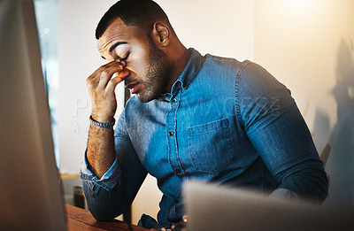 Buy stock photo Shot of a young businessman experiencing stress during a late night at work