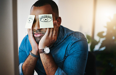 Buy stock photo Shot of a tired young businessman working late in an office with sticky notes covering his eyes