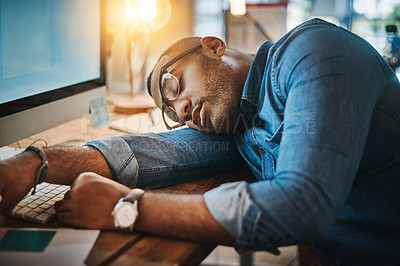 Buy stock photo Shot of an exhausted young businessman sleeping at his desk in a modern office