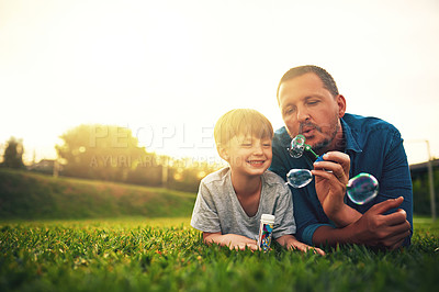 Buy stock photo Shot of a father and his adorable son blowing bubbles in the backyard