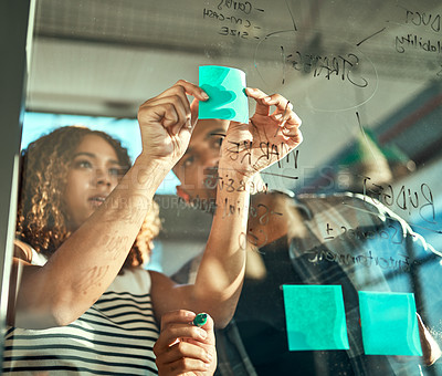 Buy stock photo Shot of two focussed young work colleagues putting up sticky notes on a glass wall while brainstorming together in the office at work